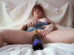 Redhead fucking a champagne bottle Thumb