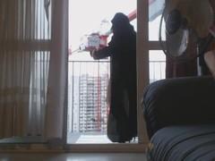 musulmane en niqab danse sur son balcon devant un grutier Thumb